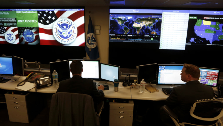 US Department of Homeland Security employees work in front of US threat level displays inside the National Cybersecurity and Communications Integration Center as part of a guided tour in Arlington, Va. June 26, 2014. (Photo by Kevin Lamarque/Reuters)