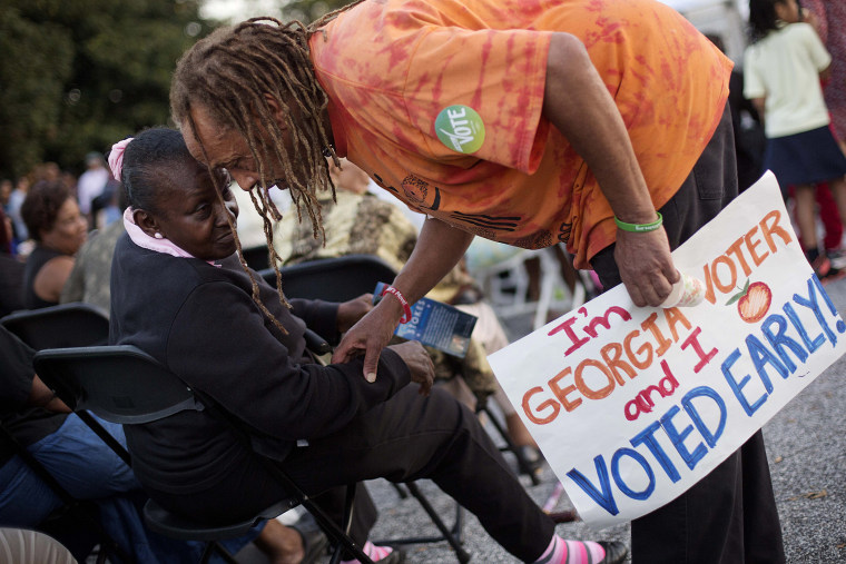 Alvin Dollar, of Decatur, right, carries a sign proclaiming he voted early as he talks with Dianna Green, of Atlanta at a Democratic rally encouraging early voting before U.S. Senate candidate Michelle Nunn takes the stage, on Oct. 27, 2014, in Decatur.