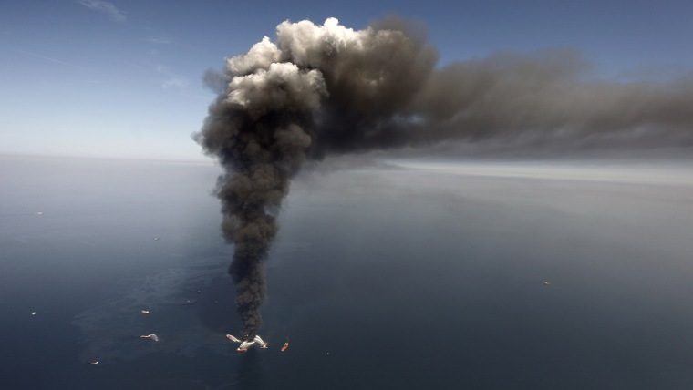 In this Wednesday, April 21, 2010 file photo, oil can be seen in the Gulf of Mexico, more than 50 miles southeast of Venice on Louisiana's tip, as a large plume of smoke rises from fires on BP's Deepwater Horizon offshore oil rig.
