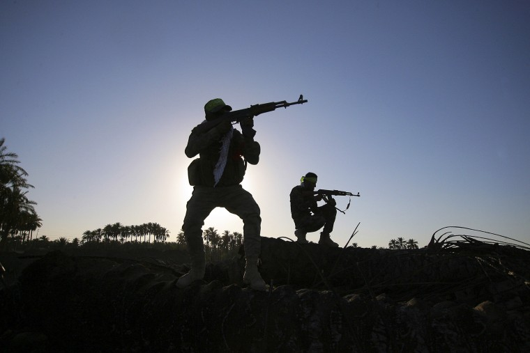 In this, Oct . 7, 2014 file photo, Iraqi Shiite militiamen aim their weapons during clashes with militants from the Islamic State group, in Jurf al-Sakhar, about 43 miles southwest of Baghdad, Iraq. (Photo by AP)