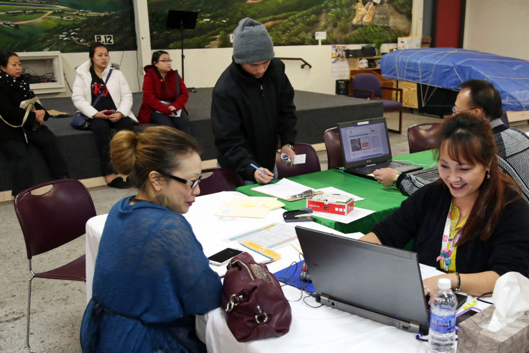 Mai Lo Lee, right, enrolls a woman in the state's insurance exchange, MNsure, as others (seated) from the Southeast Asian community wait their turn to register, on Feb. 13, 2015, in St. Paul, Minn. (Photo by Jim Mone/AP)