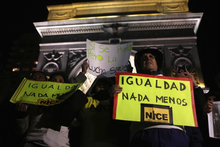 An activist holds a sign during a gathering to celebrate President Barack Obama's executive action on immigration policy in New York, N.Y., on Nov. 21, 2014. (Photo by John Moore/Getty)