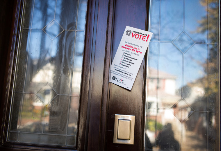 A pamphlet from the New York Immigrant Coalition is left in a door by volunteers from the Arab American Association of New York, AAANY, Nov. 4, 2014 in the Bay Ridge neighborhood of Brooklyn, N.Y. (Photo by Robert Nickelsberg/Getty)