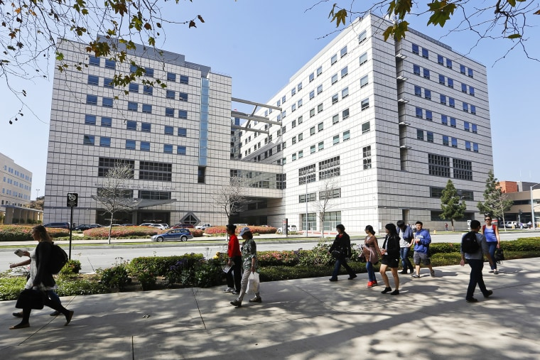 People walk near the Ronald Reagan UCLA Medical Center in Los Angeles building in Los Angeles, Calif., Feb. 19, 2015. (Photo by Damian Dovarganes/AP)