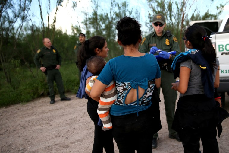 Families of Central American immigrants turn themselves in to US Border Patrol agents after crossing the Rio Grande River from Mexico on Sep. 8, 2014 to McAllen, Texas. (Photo by John Moore/Getty)