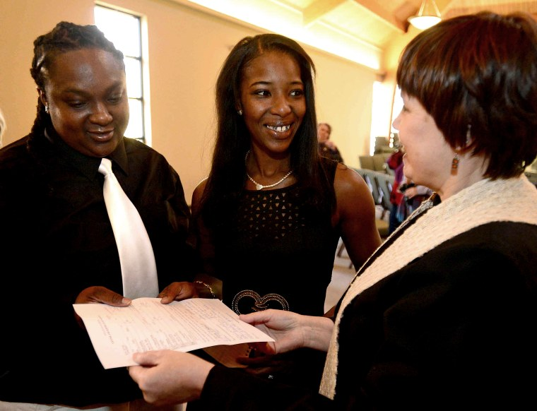 The Rev. Michelle Buhite hands Natasha Hemphill-Mayes and Leslie Mayes their marriage license after officiating the couples wedding ceremony on Nov. 23, 2014 in Spartanburg, SC. (Photo by Michael Justus/AP)