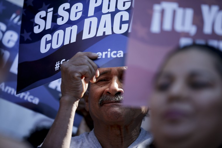 A man stands among signs during a rally in support of President Barack Obama's plan to protect more than 4 million people living illegally in the U.S. from deportation on Feb. 17, 2015, in San Diego. (Photo by Gregory Bull/AP)