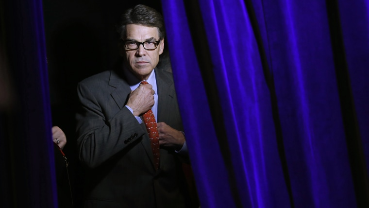 Former Governor of Texas Rick Perry adjusts his tie as he listens to his introduction from the side of the stage at an event in Des Moines, Iowa, on Jan. 24, 2015. (Photo by Jim Young/Reuters)