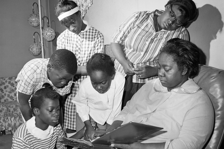 Exerlena Jackson, widow of Wharlest Jackson, ex-treasurer of the Natchez NAACP, who was killed by a bomb blast in his pickup truck, is shown with her family. (Photo by AP)