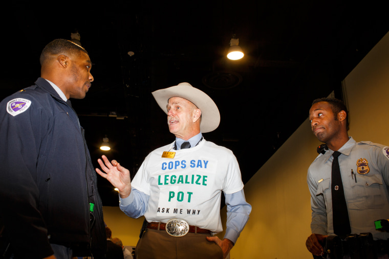 """Howard """"Cowboy"""" Wooldridge, co-founder of Law Enforcement Against Prohibition, speaks to two Prince Georges County police officers at CPAC in National Harbor, Md., on Feb. 27, 2015. (Photo by Melissa Golden/Redux for MSNBC)"""