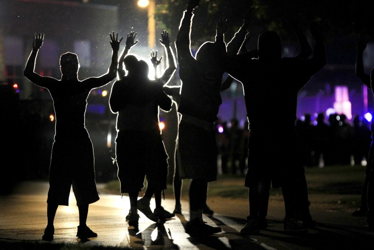 People raise their hands in the middle of the street as police wearing riot gear move toward their position trying to get them to disperse, Ferguson, Mo., Aug. 11, 2014. (Photo by Jeff Roberson/AP)