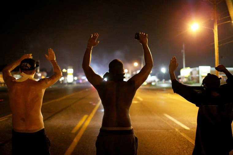 """Demonstrators raise their arms and chant, \""""Hands up, Don't Shoot\"""", as police clear them from the street as they protest the shooting death of Michael Brown on Aug. 17, 2014 in Ferguson, Mo. (Photo by Joe Raedle/Getty)"""
