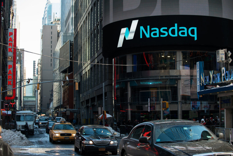 Cars drive past the NASDAQ MarketSite on March 2, 2015 in New York City.