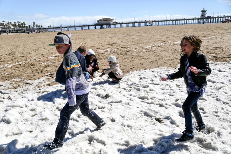 Children throw 'snowballs' after a rare hailstorm hit the sands in Huntington Beach, Calif. on March 2, 2015. (Photo by Eugene Garcia/EPA)