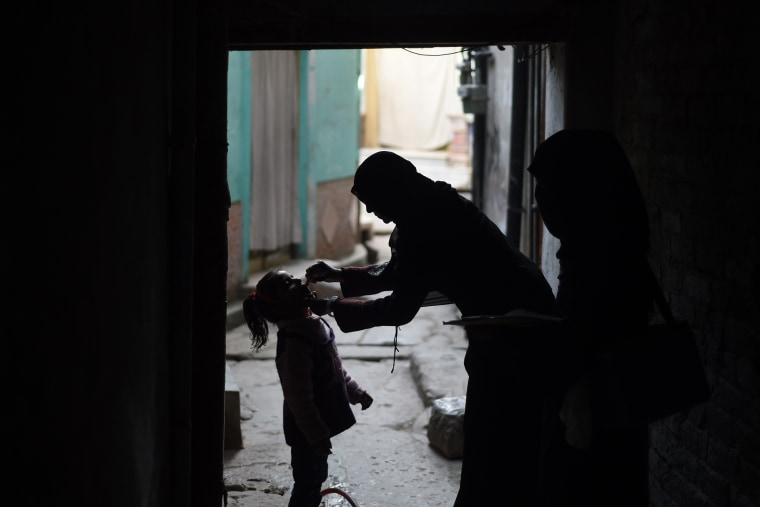 A Pakistani health worker (R) administers the polio vaccine to a child during a vaccination campaign in Rawalpindi on Dec. 9, 2014. (Photo by Farooq Naeem/AFP/Getty)