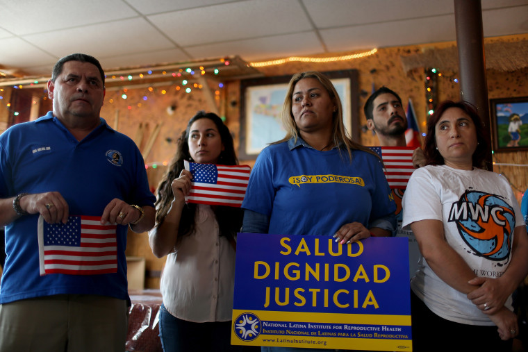 People stand together as they hold a press conference to protest the district court judge in Brownsville, Texas, who issued a preliminary injunction that temporarily blocks the implementation process of President Barack Obama's Executive Action.