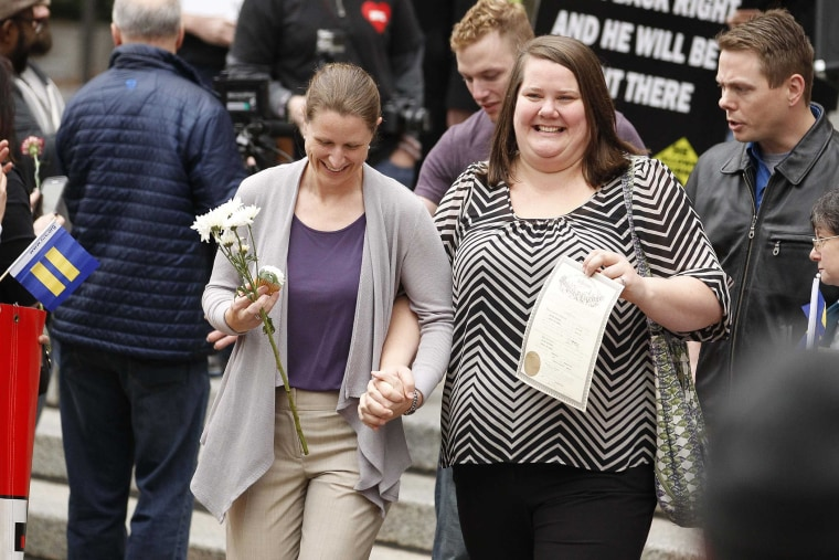 A couple displaying their marriage license reacts after receiving flowers as they leave Jefferson County Courthouse in Birmingham, Ala. in this file photo taken on Feb. 9, 2015.