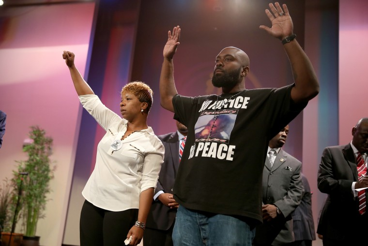 Lesley McSpadden (L) and Michael Brown, the parents of slain 18-year-old Michael Brown, acknowledge a crowd during an event at the Greater Grace Church on Aug. 17, 2014 in Ferguson, Mo. (Photo by Joe Raedle/Getty)