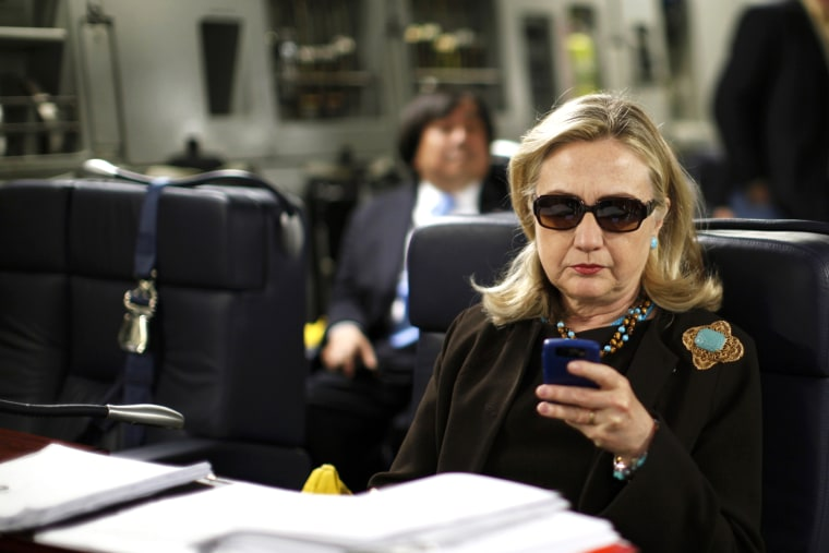 Secretary of State Hillary Clinton checks her phone upon her departure in a military plane from Malta bound for Tripoli, Libya on Oct. 18, 2011. (Photo by Kevin Lamarque/Reuters)