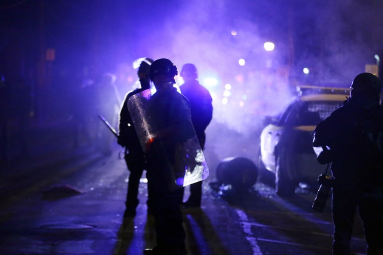 In this Nov. 25, 2014 file photo, police officers watch protesters as smoke fills the streets in Ferguson, Mo. after a grand jury's decision in the fatal shooting of Michael Brown. (Photo by Charlie Riedel/AP)
