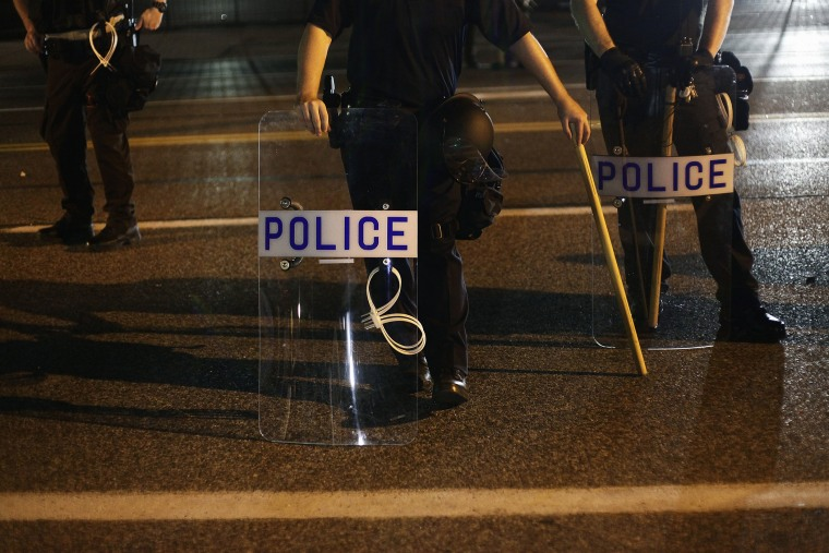 Police officers in riot gear stand in position as demonstrators protest the shooting death of Michael Brown, in Ferguson, Mo., on Aug. 19, 2014. (Photo by Joshua Lott/Reuters)