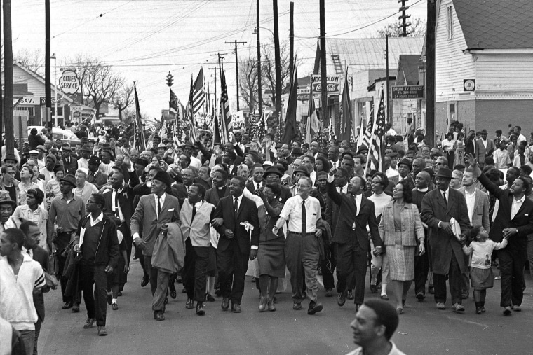 In this March 21, 1965 file photo, Dr. Martin Luther King, foreground row, fifth from right, waves as marchers stream across the Alabama River on the first of a five day, 50-mile march to the state capitol at Montgomery, Ala. (Photo by AP)