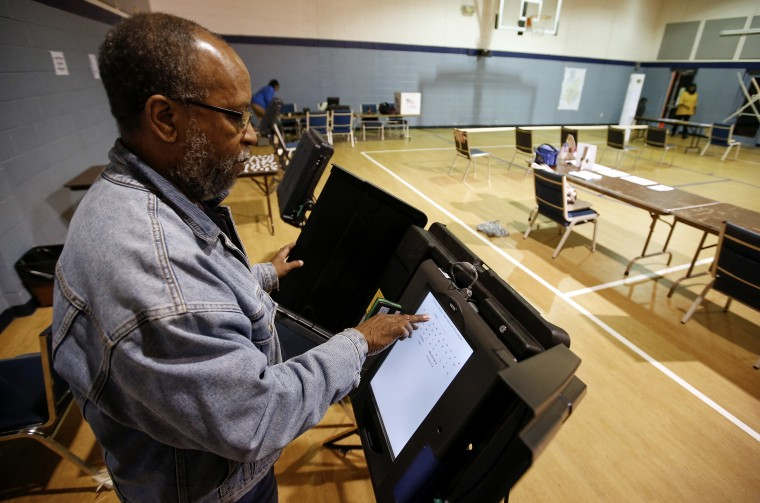Poll worker Willie Stafford Jr. programs a voting terminal before the start of the voting at the Grove Presbyterian Church in Charlotte, NC, Nov. 4, 2014. (Photo by Chris Keane/Reuters)