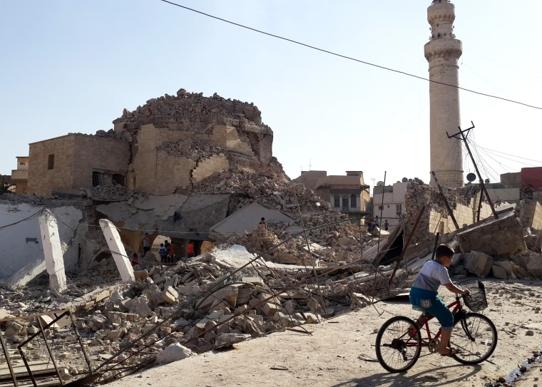 A bicyclist rides by the remnants of the old Mosque of The Prophet Jirjis, destroyed by Islamic State militants, in central Mosul, Iraq, on July 27, 2014. (File Photo/AP)