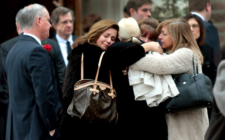Family members of Missouri State Auditor Tom Schweich embrace outside The Church of St. Michael and St. George in Clayton, Mo., after his funeral on March 3, 2015. (Photo by Robert Cohen/St. Louis Post-Dispatch via AP)