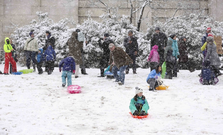 Children sled on the west lawn of the U.S. Capitol during a snow storm in Washington
