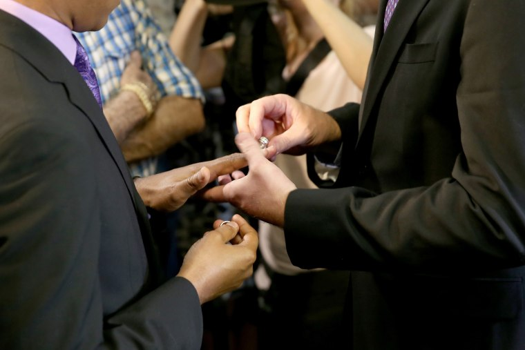 Newlyweds Jeff Delmay and Todd Delmay (L-R) exchange rings during a marriage ceremony in the Miami-Dade court room of Circuit Judge Sarah Zabel on Jan. 5, 2015 in Miami, Fla.