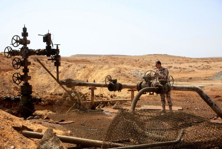 Syrian government soldier stands next to a well at Jazel oil field, after retaking the area from Islamic State fighters on March 9, 2015. Recent US-led coalition air strikes have frequently targeted oil facilities run by IS. (Photo by STR/AFP/Getty)