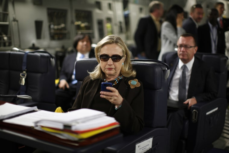 Then-Secretary of State Hillary Rodham Clinton checks her Blackberry from a desk inside a C-17 military plane upon her departure from Malta, in the Mediterranean Sea, bound for Tripoli, Libya on Oct. 18, 2011. (Photo by Kevin Lamarque/Pool/AP)