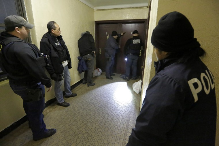 Immigration and Customs Enforcement officers try to gain entry to an apartment, in the Bronx borough of New York, during a series of early-morning arrests, March 3, 2015. (Photo by Richard Drew/AP)