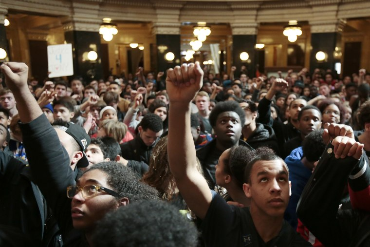 Demonstrators raise their fists to protest the shooting of Tony Robinson at the state Capitol Monday on March 9, 2015, in Madison, Wis. (Photo by Michael P. King/Wisconsin State Journal/AP)