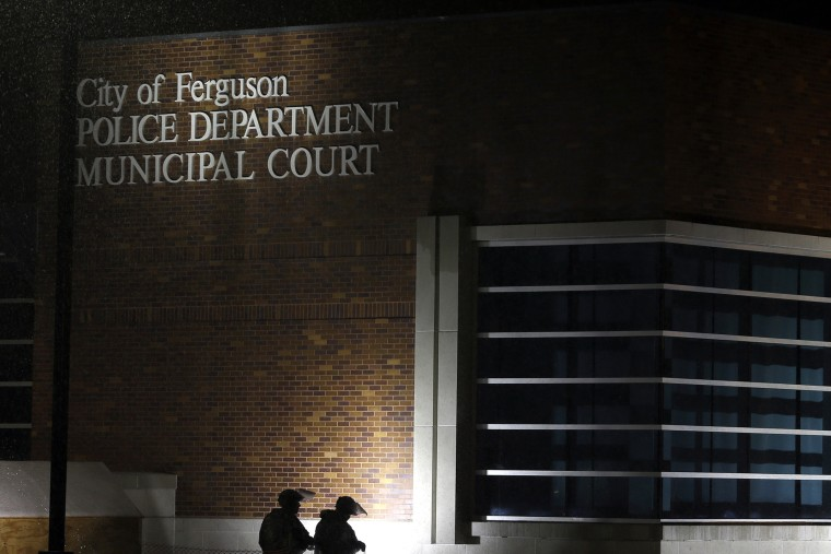 Members of Missouri National Guard stand outside of the Ferguson Police Department and the Municipal Court in Ferguson, Mo. on Nov. 26, 2014. (Photo by Jeff Roberson/AP)