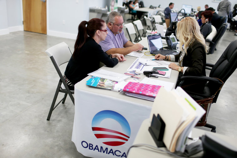 Aymara Marchante (L) and Wiktor Garcia sit with Maria Elena Santa Coloma,(R) an insurance advisor with UniVista Insurance company, as they sign up for the Affordable Care Act on Feb. 5, 2015 in Miami, Fla. (Photo by Joe Raedle/Getty)