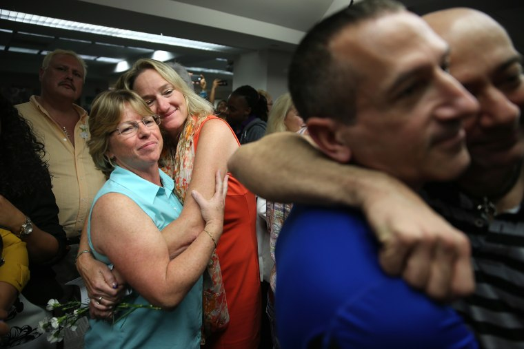 Couples embrace as they attend a wedding ceremony at the Broward County Courthouse on Jan. 6, 2015 in Fort Lauderdale, Fla. (Photo by Joe Raedle/Getty)
