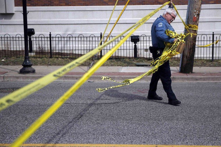A police officer walks under the tape marking the perimeter around the Ferguson Police Department in Ferguson, Missouri on March 12, 2015.