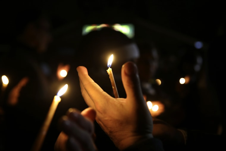 People take part in a candlelight vigil on March 12, 2015, in Ferguson, Mo.