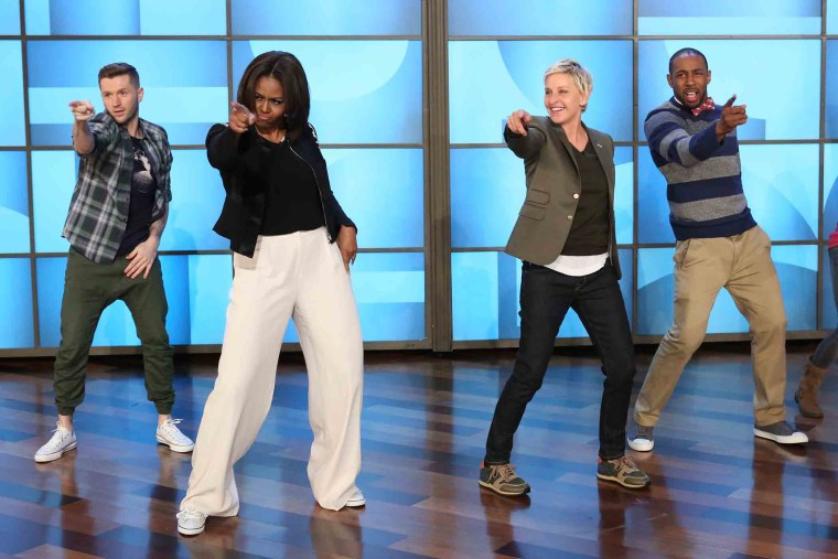 n this photo released by Warner Bros., talk show host Ellen DeGeneres, second right, dances with first lady Michelle Obama's as she takes part in Obama's #GimmeFive Challenge. (Photo by Mike Rozman/Warner Bros./AP)