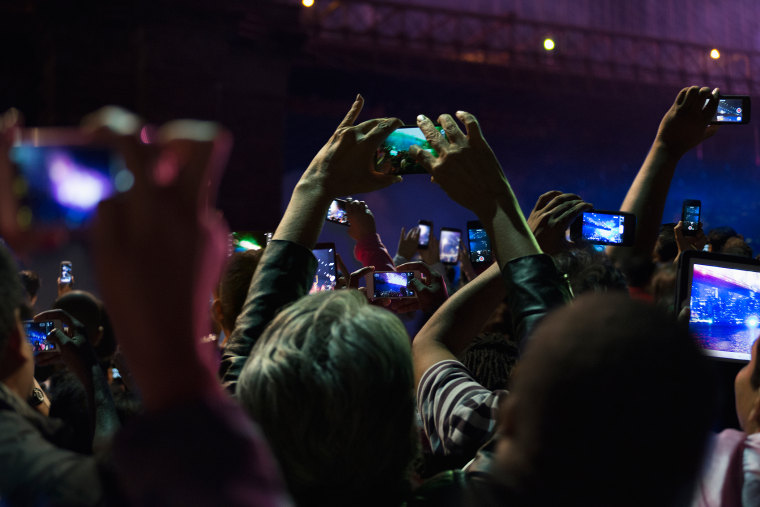 People in crowd take photos on their cell phones at night. (Photo by GS/Gallery Stock)