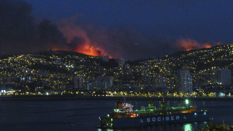 Smoke from a forest fire is seen in Valparaiso city, northwest of Santiago, Chile, March 13, 2015. A forest fire was raging out of control on Friday evening into Saturday, threatening the Chilean port city of Valparaiso. (Photo by Lucas Alvarado/Reuters)