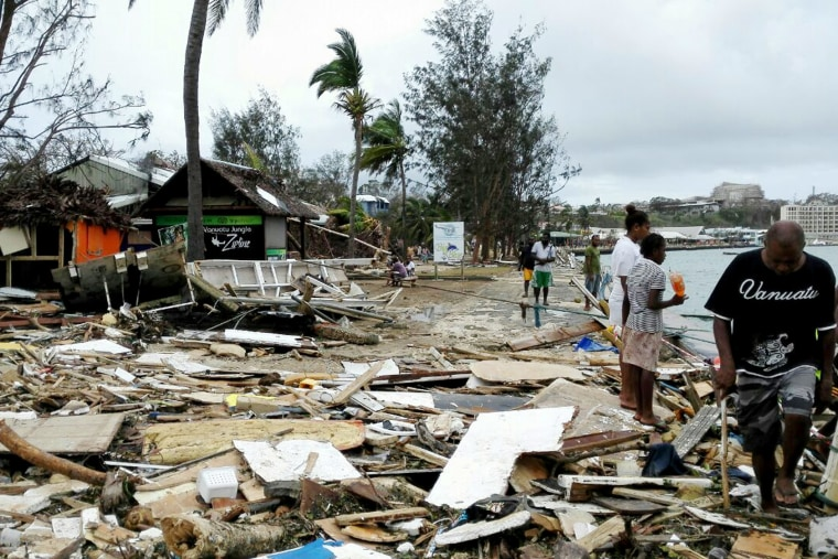 In this photo provided by China's Xinhua News Agency, locals walk past debris in Port Vila, Vanuatu, after Cyclone Pam ripped through the tiny South Pacific archipelago, March 15, 2015. (Photo by Luo Xiangfeng/Xinhua via AP)