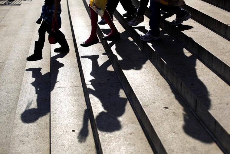 School children walk down the steps of a school.