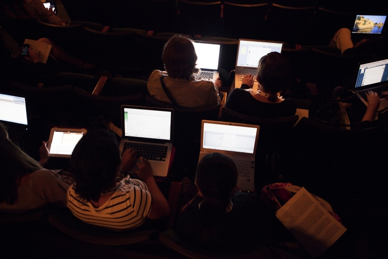 People work on their laptops while attending a lecture. (Photo by Martin Adolfsson/Gallery Stock)