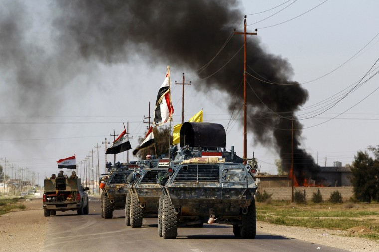 Armored vehicles of Iraqi security forces with militias known as Hashid Shaabi are driven past smoke arising from a clash with Islamic State militants in the town of al-Alam, Tikrit, March 10, 2015. (Photo by Thaier Al-Sudani/Reuters)