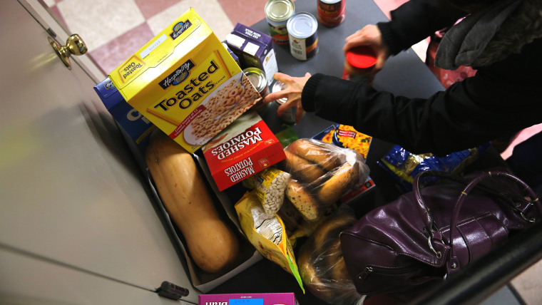 People receive free groceries at a food pantry run by the Food Bank For New York City on Dec. 11, 2013 in New York City.