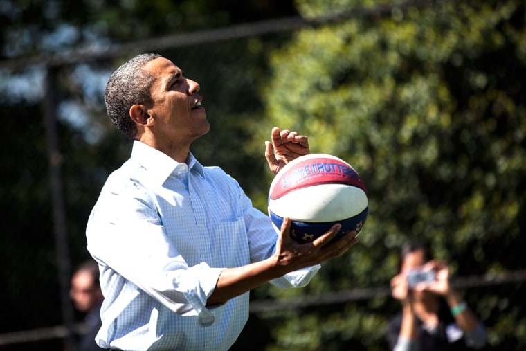President Barack Obama shoots a basketball while participating in a basketball station with the Harlem Globetrotters during the annual Easter Egg Roll on the South Lawn of the White House April 9, 2012 in Washington, D.C. (Photo by Brendan Smialowski/AFP/