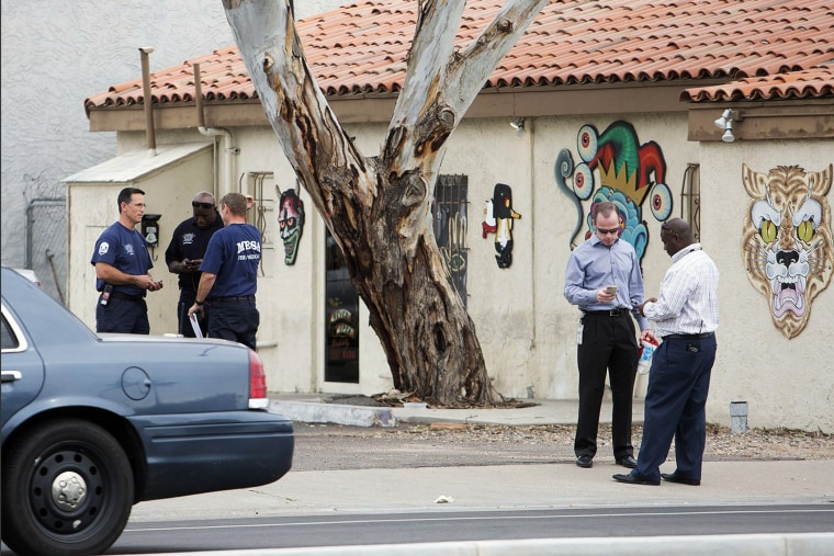 Police confer near a tattoo parlor at one of the scenes of a multiple location shooting that has injured at least four people in Mesa, Arizona on March 18, 2015.